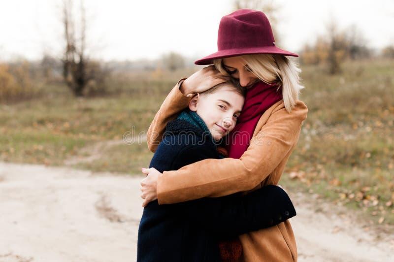 La giovane madre in un cappello rosso abbraccia suo figlio immagini stock libere da diritti