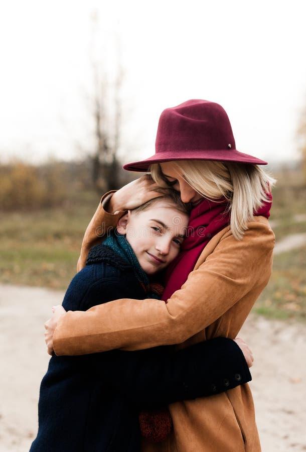 La giovane madre in un cappello rosso abbraccia suo figlio fotografia stock