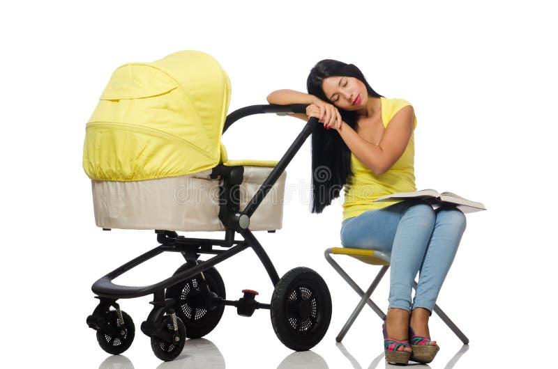 La giovane mamma con il libro di lettura della carrozzina e del bambino fotografie stock