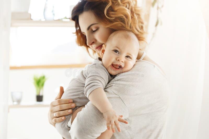 La giovane mamma felice tiene il piccolo bambino prezioso e delicatamente abbracciare il suo piccolo corpo Bambino che ride alleg fotografie stock