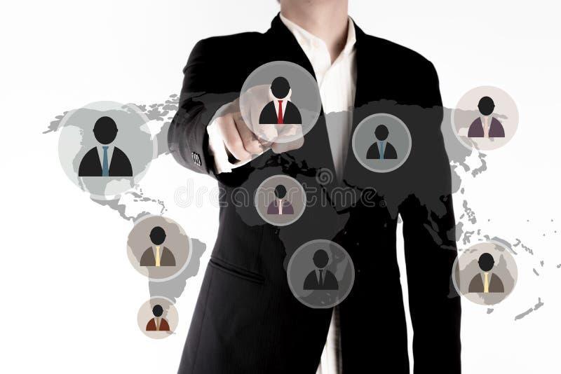 La giovane mano dell'uomo di affari ha indicato all'interfaccia dell'icona dell'uomo di affari in paese differente fotografia stock libera da diritti