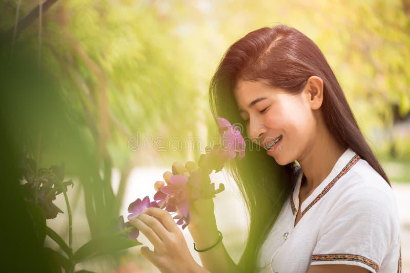 La giovane orchidea asiatica felice della tenuta della donna con un sorriso felice dentro graden immagini stock libere da diritti