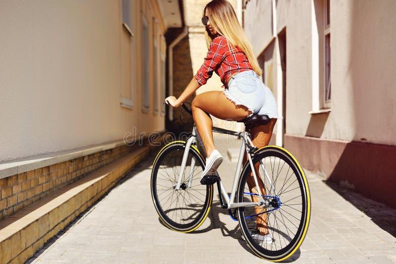 La giovane parte posteriore sexy della donna sullo sport ha riparato la bicicletta dell'ingranaggio che posa sul outd immagini stock libere da diritti