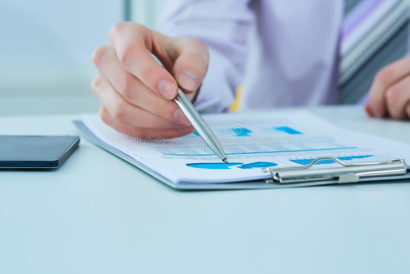La giovane penna di tenuta della mano dell'uomo di affari ed il grafico del grafico indicante per analizzano la società le vendit immagine stock