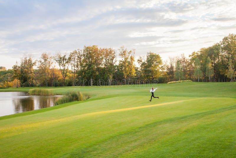 La giovane ragazza adulta funziona sull'erba verde del campo da golf E fotografie stock