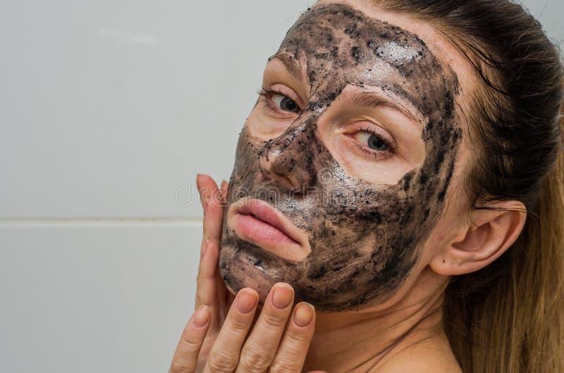 La giovane ragazza affascinante fa una maschera nera del carbone sul suo fronte fotografie stock