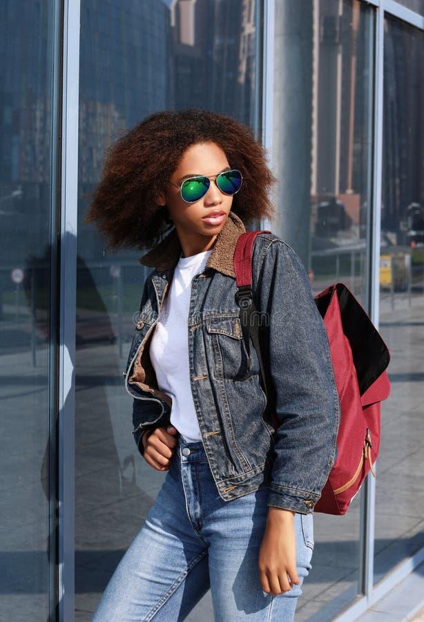 La giovane ragazza afroamericana in occhiali da sole, posanti all'aperto, ha vestito casuale, con brevi capelli voluminosi immagine stock