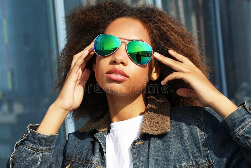 La giovane ragazza afroamericana in occhiali da sole, posanti all'aperto, ha vestito casuale, con brevi capelli voluminosi fotografia stock