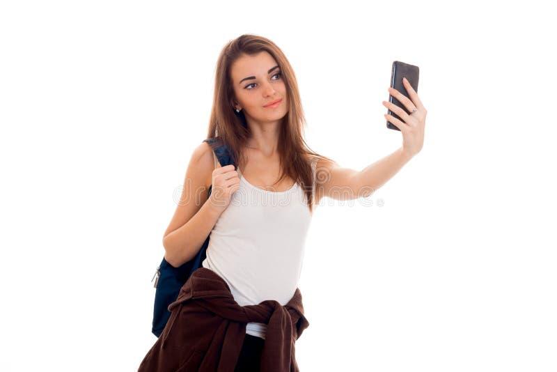 La giovane ragazza allegra dello studente con lo zaino fa il selfie sul suo telefono cellulare isolato su fondo bianco anni dello fotografia stock