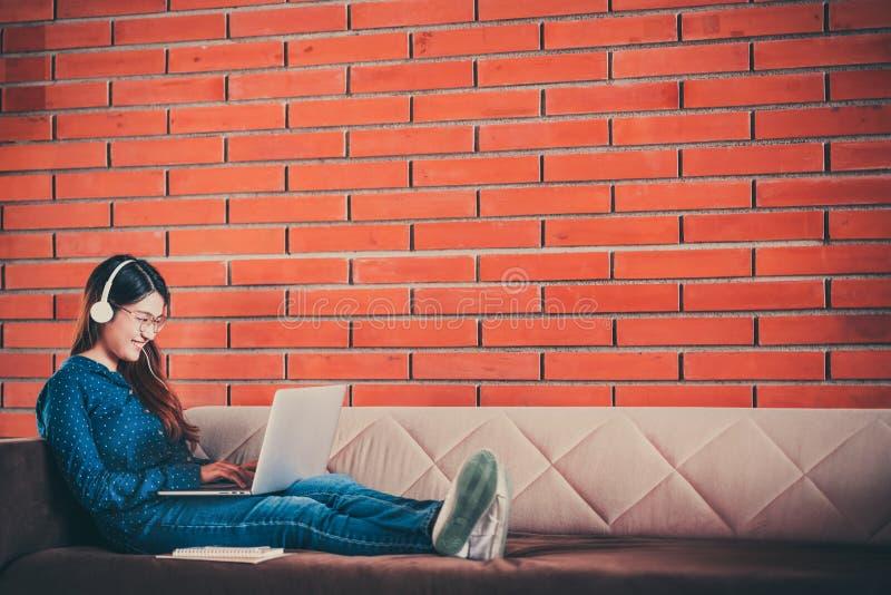 La giovane ragazza asiatica dello studente di college che per mezzo del computer portatile, la cuffia, lo smartphone, taccuino su immagine stock libera da diritti