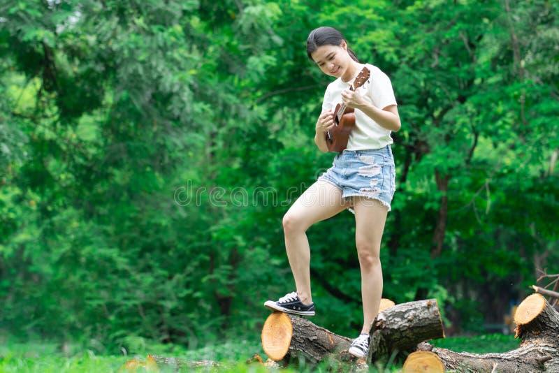 La giovane ragazza asiatica deve godere di di giocare la chitarra nella foresta immagini stock