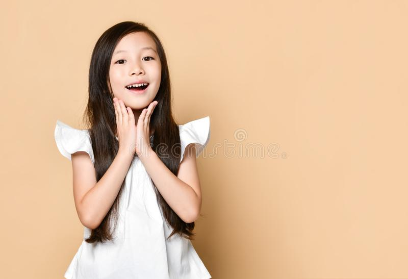 La giovane ragazza asiatica ha sorpreso i grida felici emozionanti Bambino allegro con l'espressione allegra divertente del front fotografia stock libera da diritti