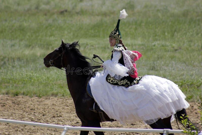 La giovane ragazza asiatica in vestiti tradizionali sta montando il suo cavallo puro della razza in steppa del Kazakistan fotografia stock libera da diritti