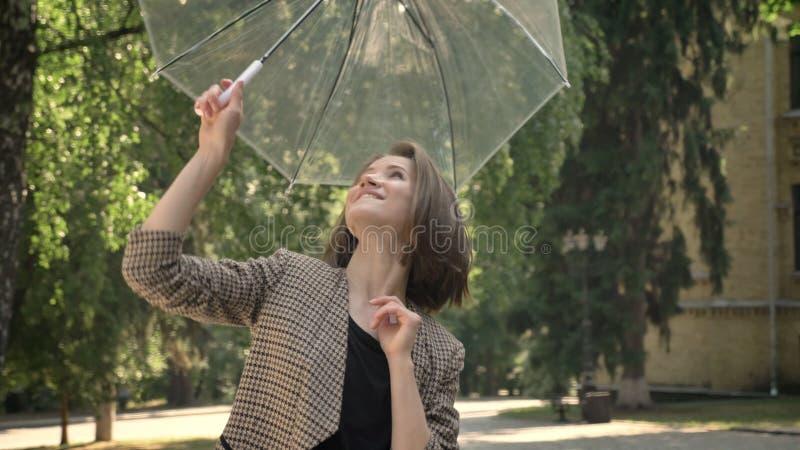 La giovane ragazza attraente apre e fila l'ombrello in parco di giorno, di estate, guardante alla macchina fotografica fotografie stock libere da diritti