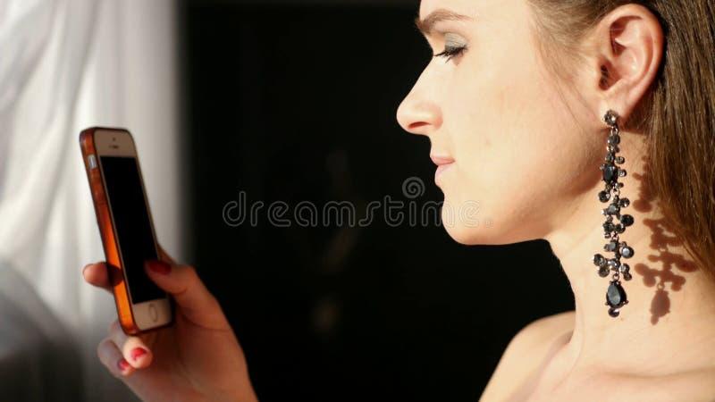 La giovane ragazza attraente in bei orecchini lunghi, sta tenendo un telefono, sta sorridendo e scrivendo un messaggio immagine stock