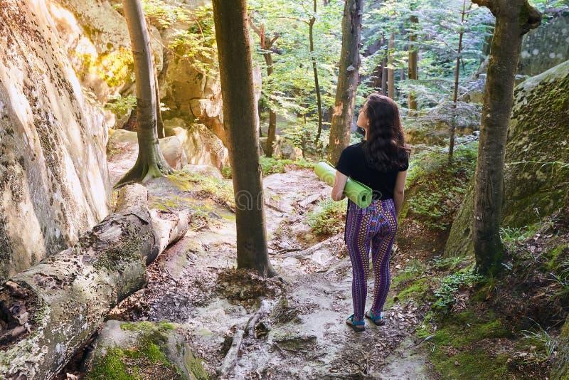 La giovane ragazza attraente nella foresta della montagna alla luce del sole sta tenendo una stuoia di yoga immagini stock
