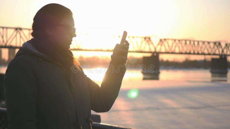La giovane ragazza attraente sta camminando lungo il lungomare sui precedenti di un ponte ferroviario e di bello tramonto immagine stock