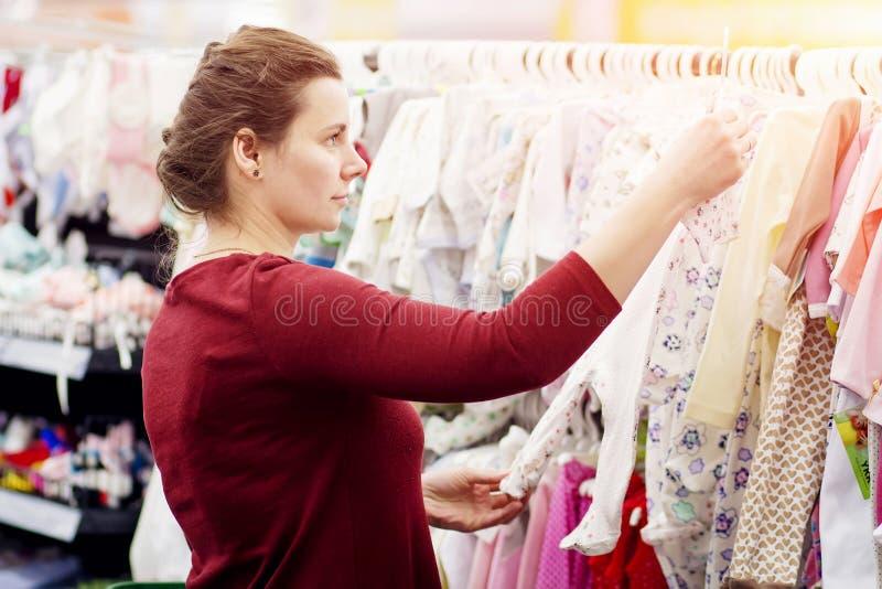 La giovane ragazza attraente sta scegliendo i vestiti nel centro commerciale Provi sopra i vestiti sul gancio nel deposito Vestit fotografia stock libera da diritti