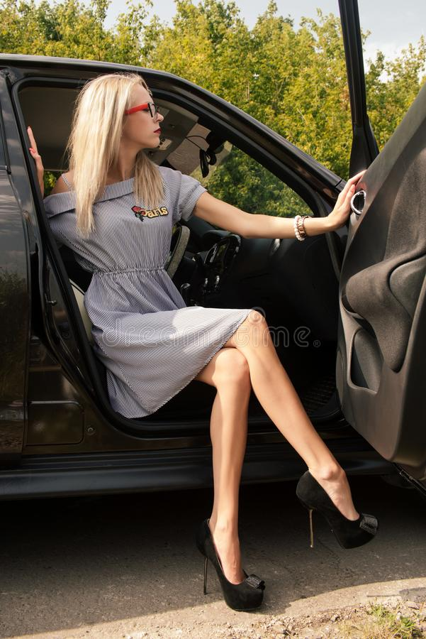 La giovane ragazza attraente in vetri ha barrato il vestito e le scarpe a tacco alto si siede nell'automobile che apre la porta fotografie stock