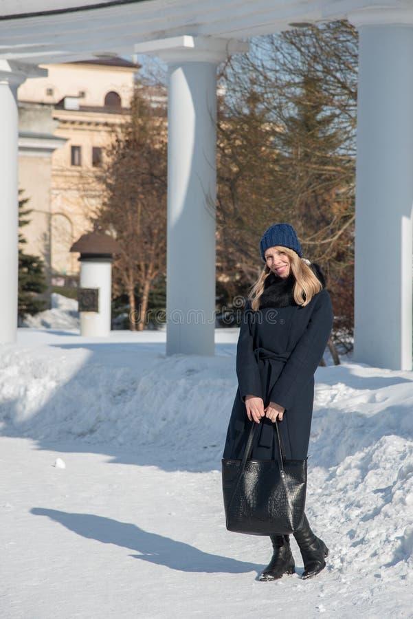 La giovane ragazza bionda in cappotto blu con pelliccia in un cappuccio tricottato con una grande borsa nera cammina attraverso l fotografie stock