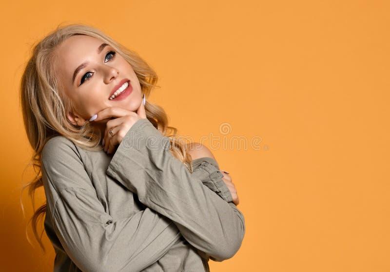 La giovane ragazza bionda in jeans lacerati tiene il suo mento e pensa più o sogno a qualcosa su fondo giallo fotografia stock libera da diritti