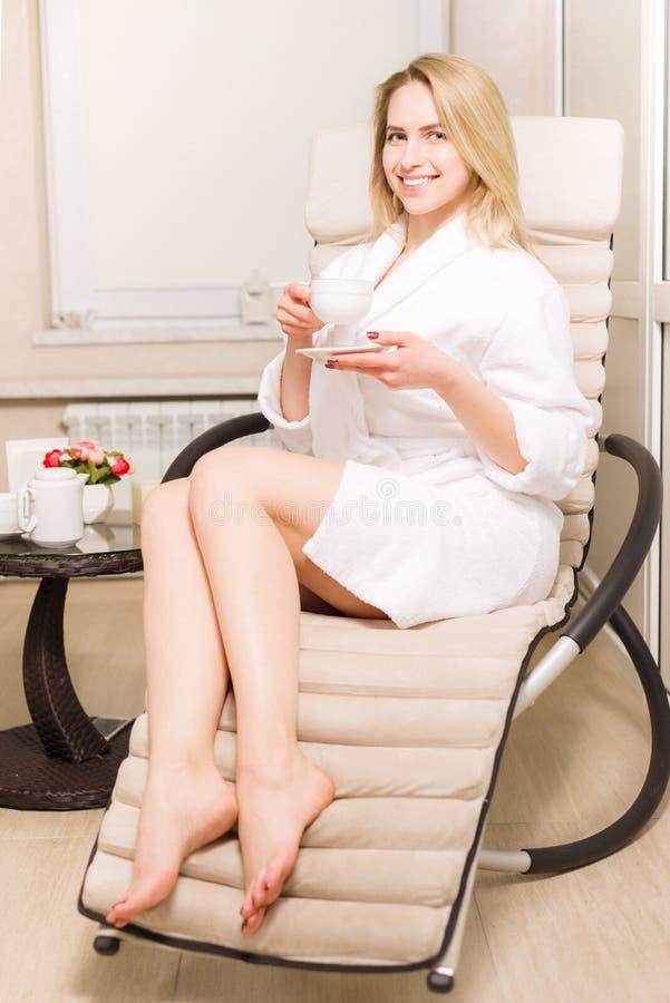 La giovane ragazza bionda sta bevendo il tè nel salone della stazione termale donna in camice che tengono una tazza in sue mani fotografia stock libera da diritti