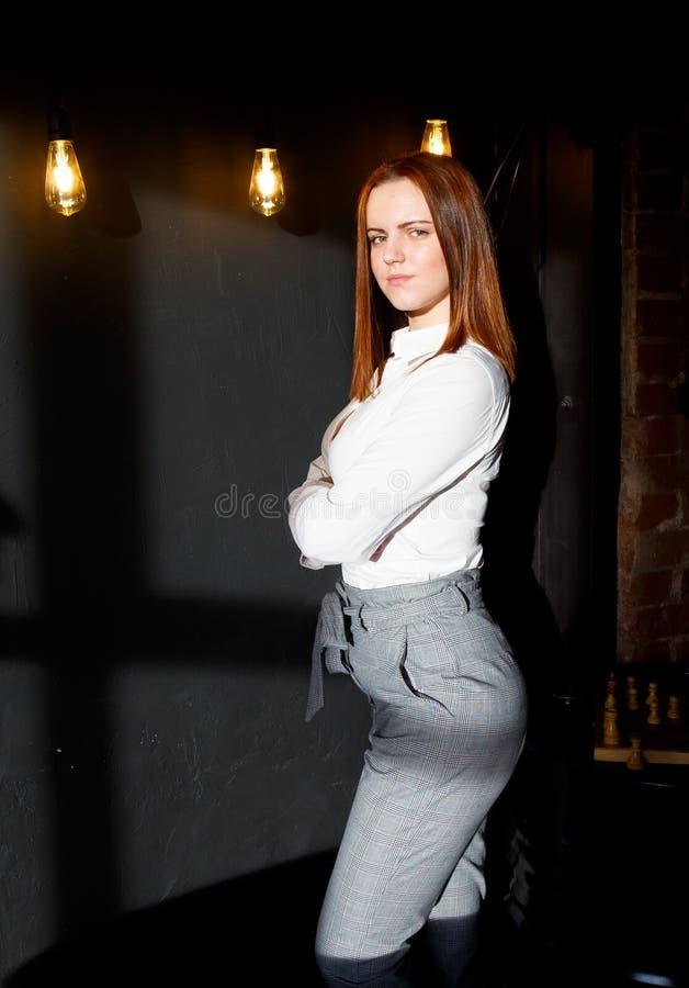La giovane ragazza dai capelli rossi alla moda sta in entrata dell'interno del sottotetto sui precedenti delle lampadine d'ardore immagine stock libera da diritti