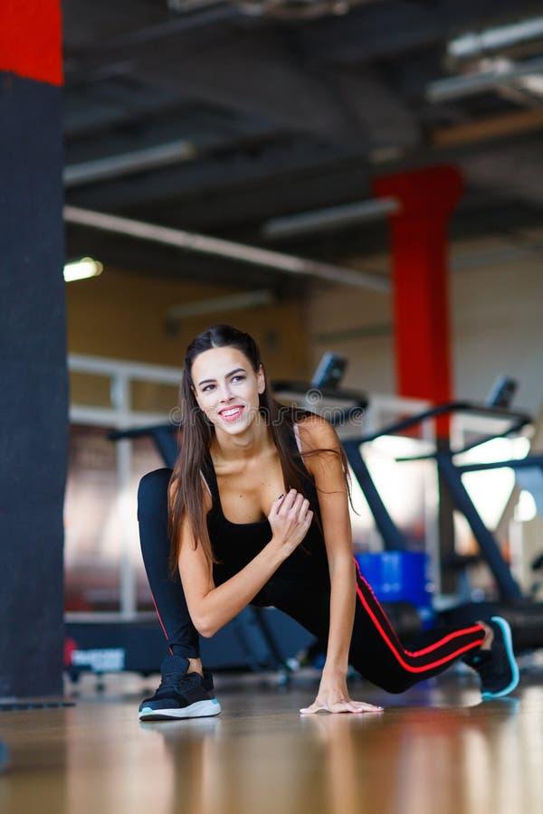 La giovane ragazza degli atleti fa gli esercizi alla palestra Concetto di sport immagine stock libera da diritti