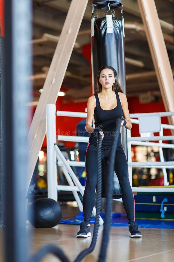 La giovane ragazza degli atleti fa gli esercizi alla palestra Concetto di sport fotografie stock