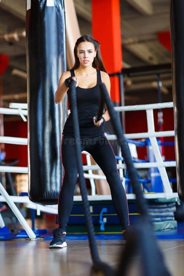 La giovane ragazza degli atleti fa gli esercizi alla palestra Concetto di sport fotografia stock