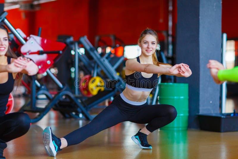 La giovane ragazza degli atleti fa gli esercizi alla palestra Concetto di sport fotografia stock libera da diritti