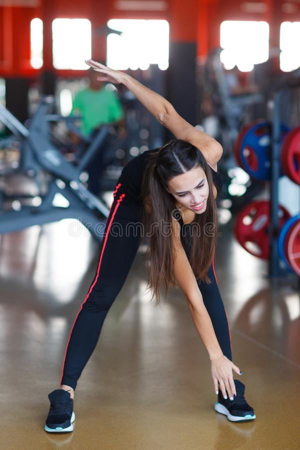La giovane ragazza degli atleti fa gli esercizi alla palestra Concetto di sport immagine stock