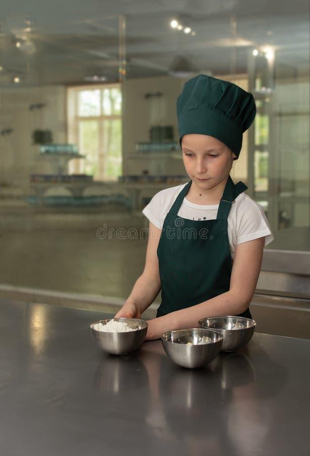 La giovane ragazza del cuoco unico del cuoco in cappuccio verde del cuoco unico mescola gli ingredienti per il dolce fotografie stock libere da diritti