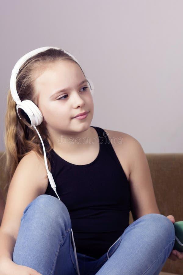 La giovane ragazza dell'adolescente ascolta musica dal telefono in cuffie a casa immagine stock libera da diritti