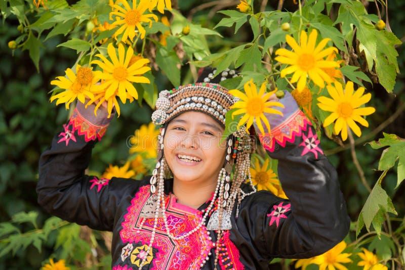 La giovane ragazza della tribù della collina di bello sorriso in girasoli fa il giardinaggio fotografia stock