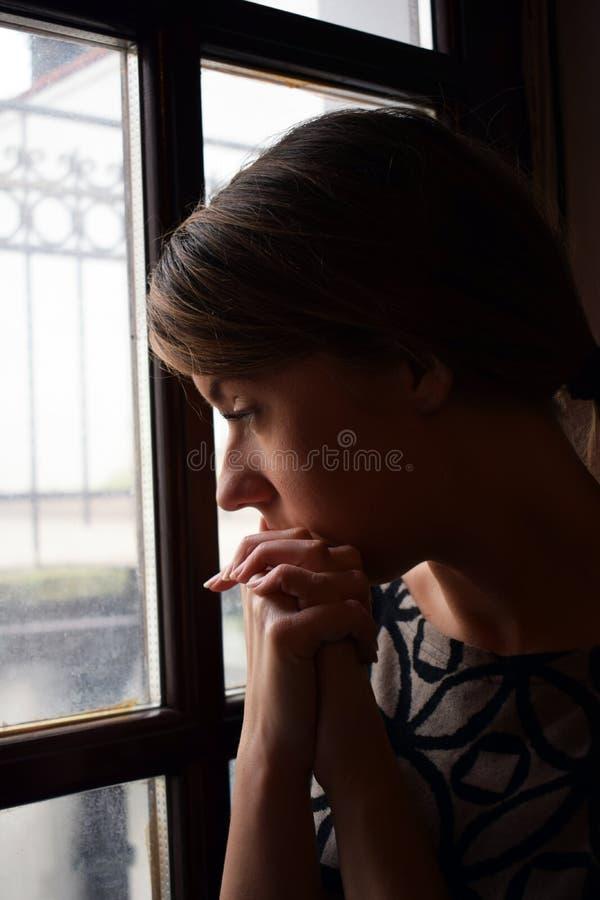 La giovane ragazza depressa è pensante e guardante fuori la finestra È triste fotografia stock libera da diritti
