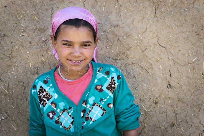 La giovane ragazza di berbero posa davanti alla sua casa in un piccolo villaggio di berbero nella valle di Ziz, vicino a Errachid immagine stock libera da diritti