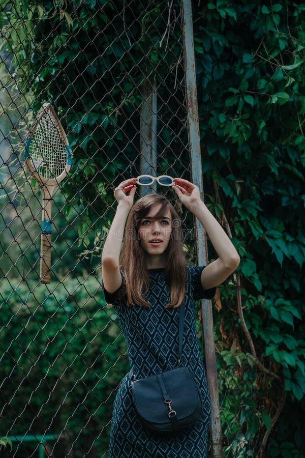 La giovane ragazza esile sta davanti al campo da tennis fotografia stock