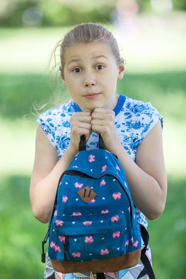 La giovane ragazza graziosa con gli occhi spalancati stringe a sé la borsa al corpo, stress emotivo fotografie stock libere da diritti