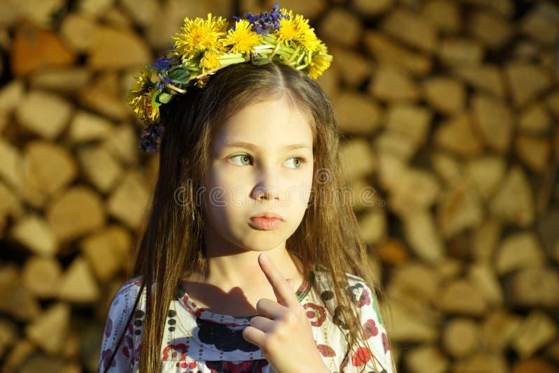 La giovane ragazza graziosa in corona dei fiori sta restando vicino alla catasta di legna nel villaggio fotografia stock libera da diritti