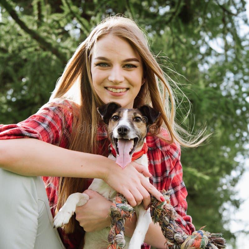 La giovane ragazza graziosa sorridente abbraccia il suo cane fotografia stock libera da diritti