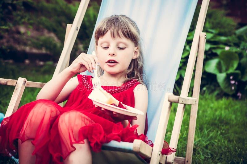 La giovane ragazza manierata in vestito rosso che si rilassa nelle chaise longue mangia il dolce durante il partito all'aperto ne immagini stock libere da diritti