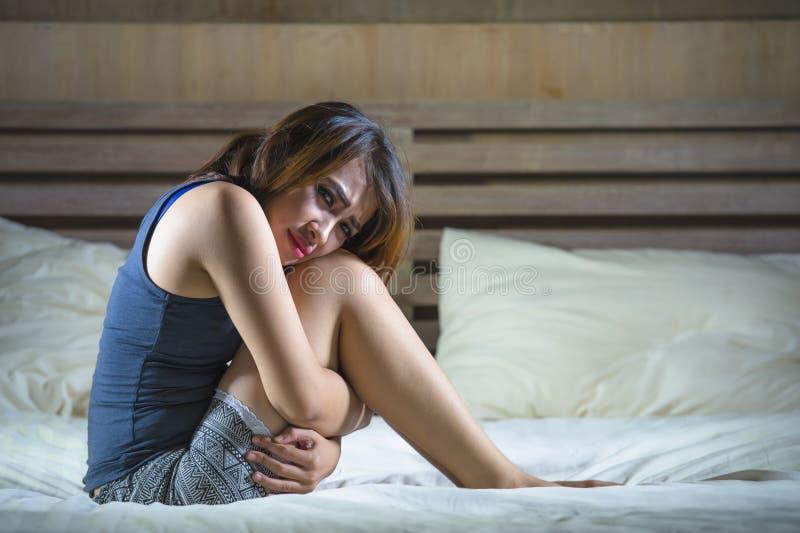 La giovane ragazza mista ispanica asiatica attraente che si siedono sul dolore di sofferenza del crampo di stomaco del letto ed i immagini stock libere da diritti