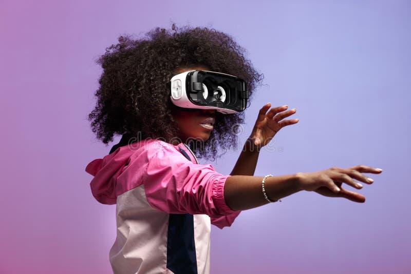 La giovane ragazza riccia castana del MOD vestita nel rivestimento di sport rosa utilizza i vetri di realt? virtuale nello studio fotografia stock