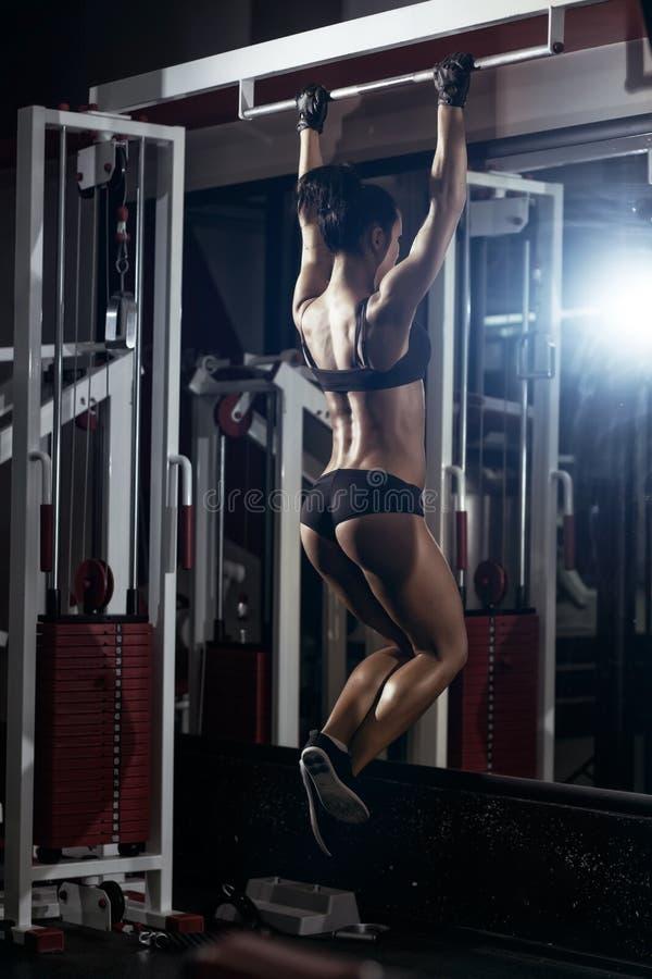 La giovane ragazza sexy di forma fisica tira su nella palestra immagini stock