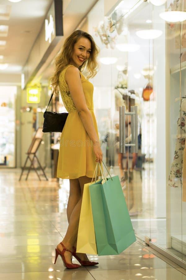 La giovane ragazza sorridente attraente in vestito giallo sta camminando nel centro commerciale con i sacchetti della spesa fotografia stock libera da diritti