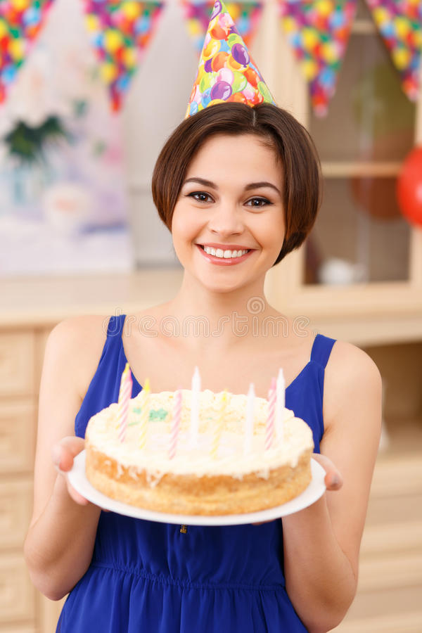 La giovane ragazza sorridente sta tenendo la sua torta di compleanno fotografia stock libera da diritti