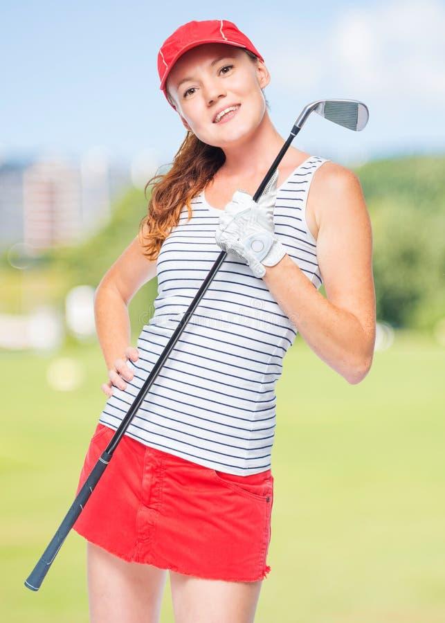 La giovane ragazza sportiva gode di di giocare il golf immagini stock