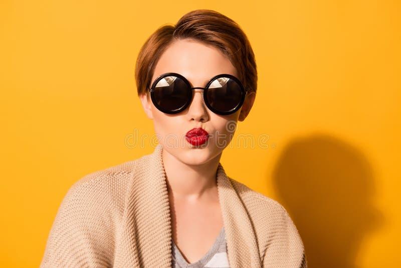 La giovane ragazza sveglia alla moda in occhiali da sole d'avanguardia invia un bacio a immagine stock