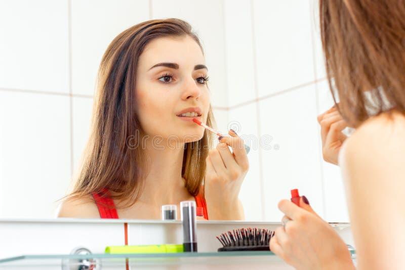 La giovane ragazza sveglia sta vicino agli specchi e colora la lucentezza del labbro immagini stock libere da diritti